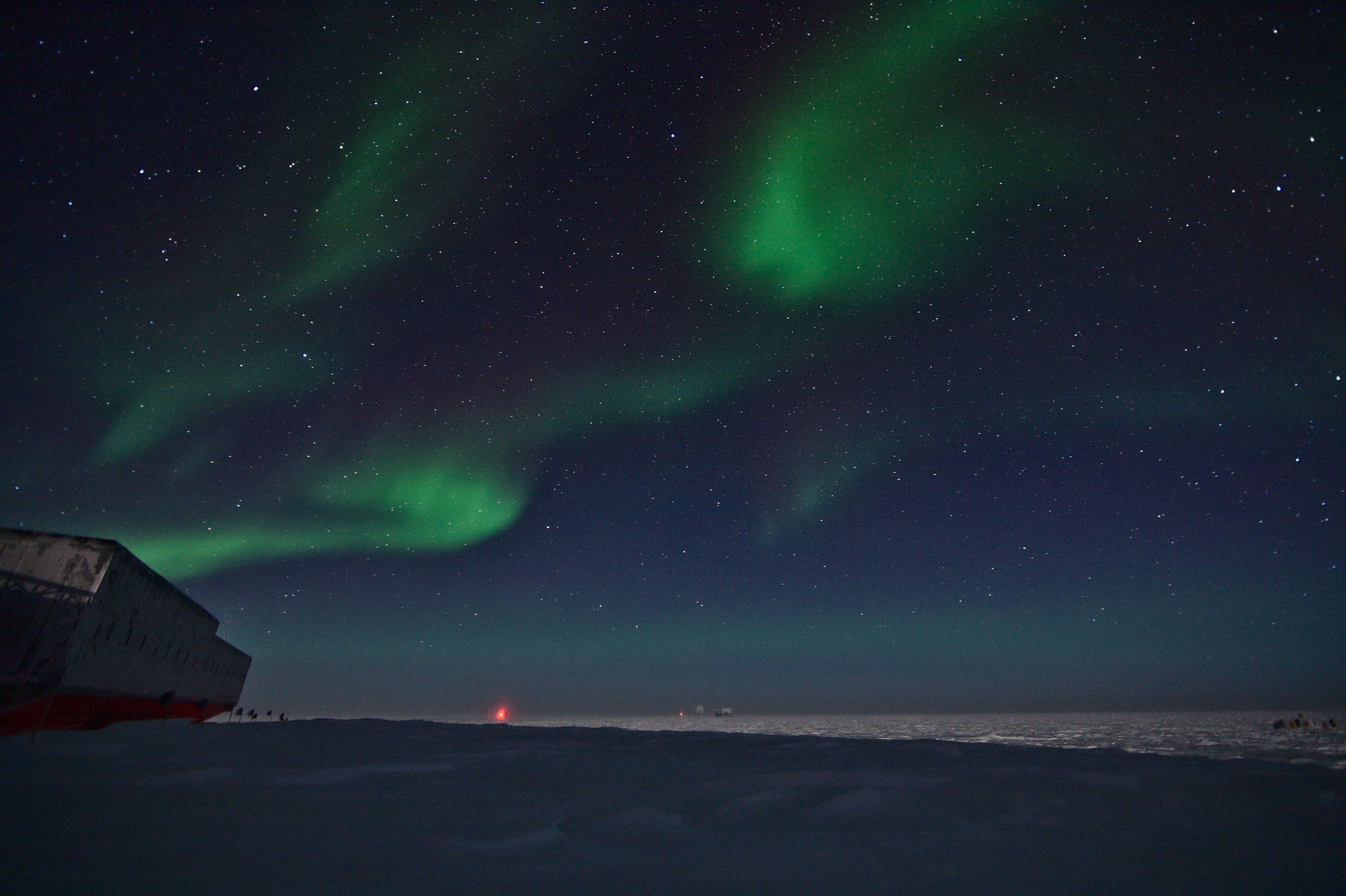 The frozen landscape behind the station illuminated by moon light and auroras