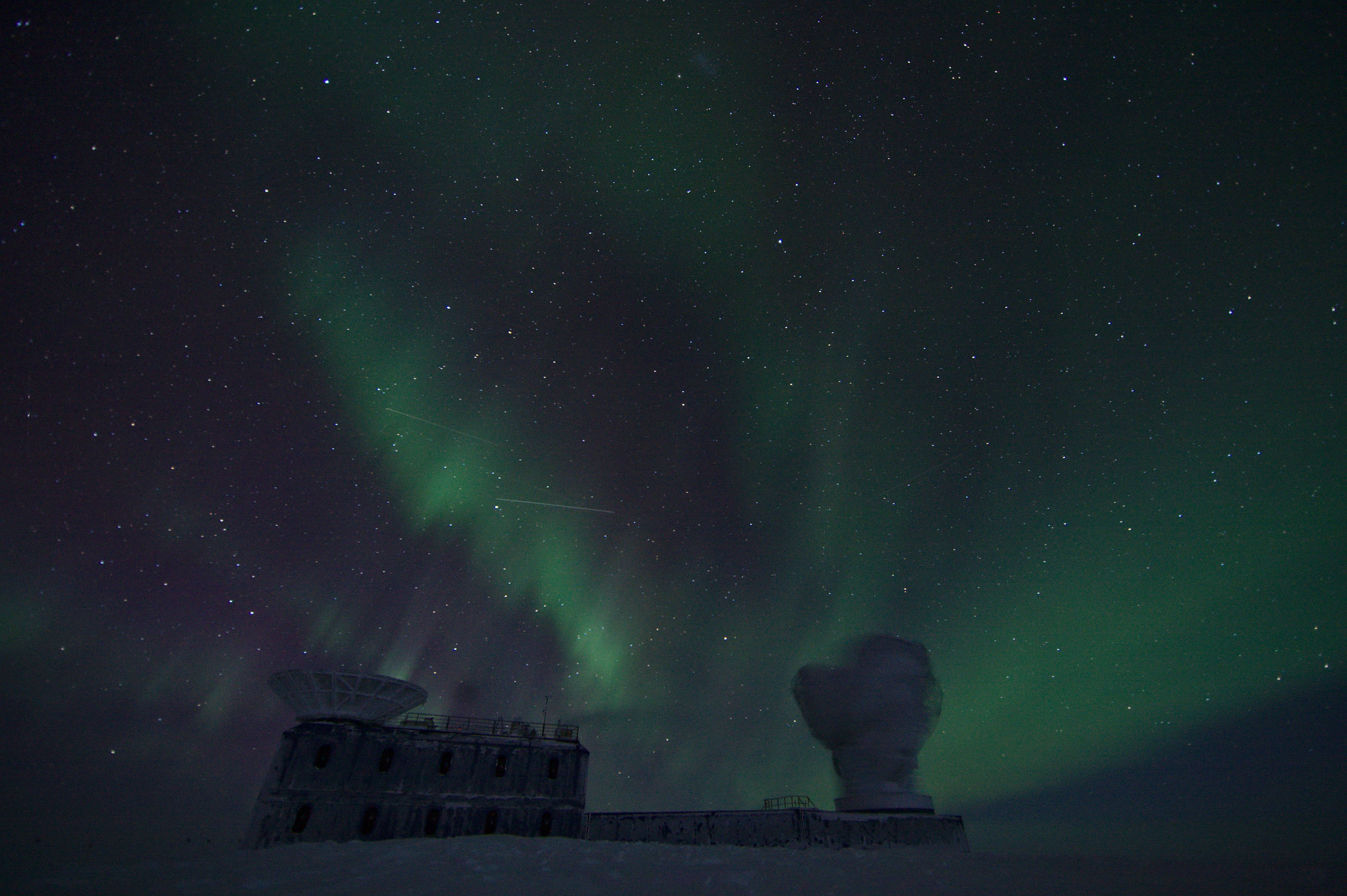 Auroras illuminate the sky while the South Pole Telescope performs CMB field observations. The Small Magellanic Cloud is visible in the very top of the picture.