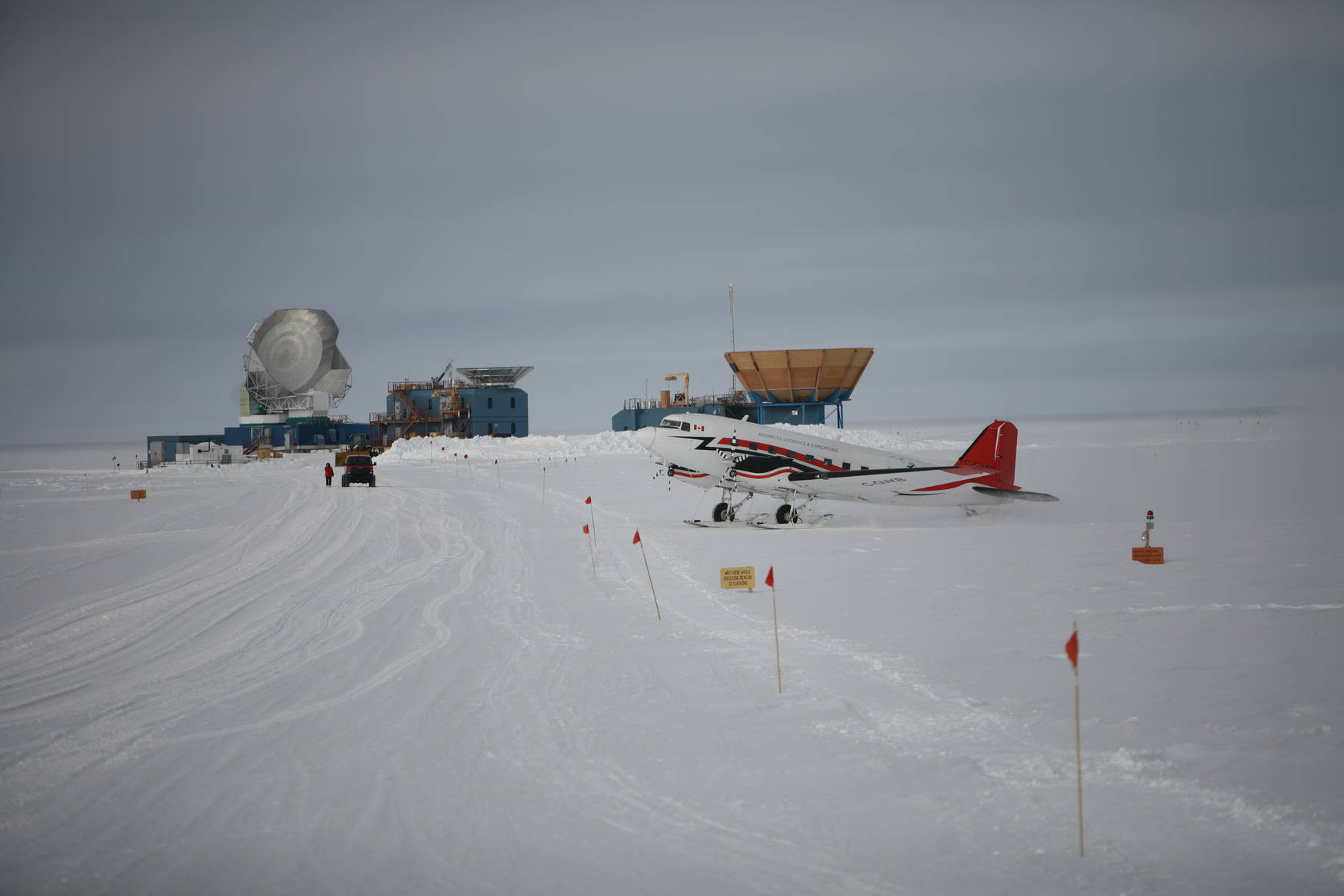 A ski-equipped Basler aircraft picking up the crew of the tourist camp to take them to their next adventure. In the background: the South Pole Telescope (left), BICEPS-3 (middle), Keck (right).