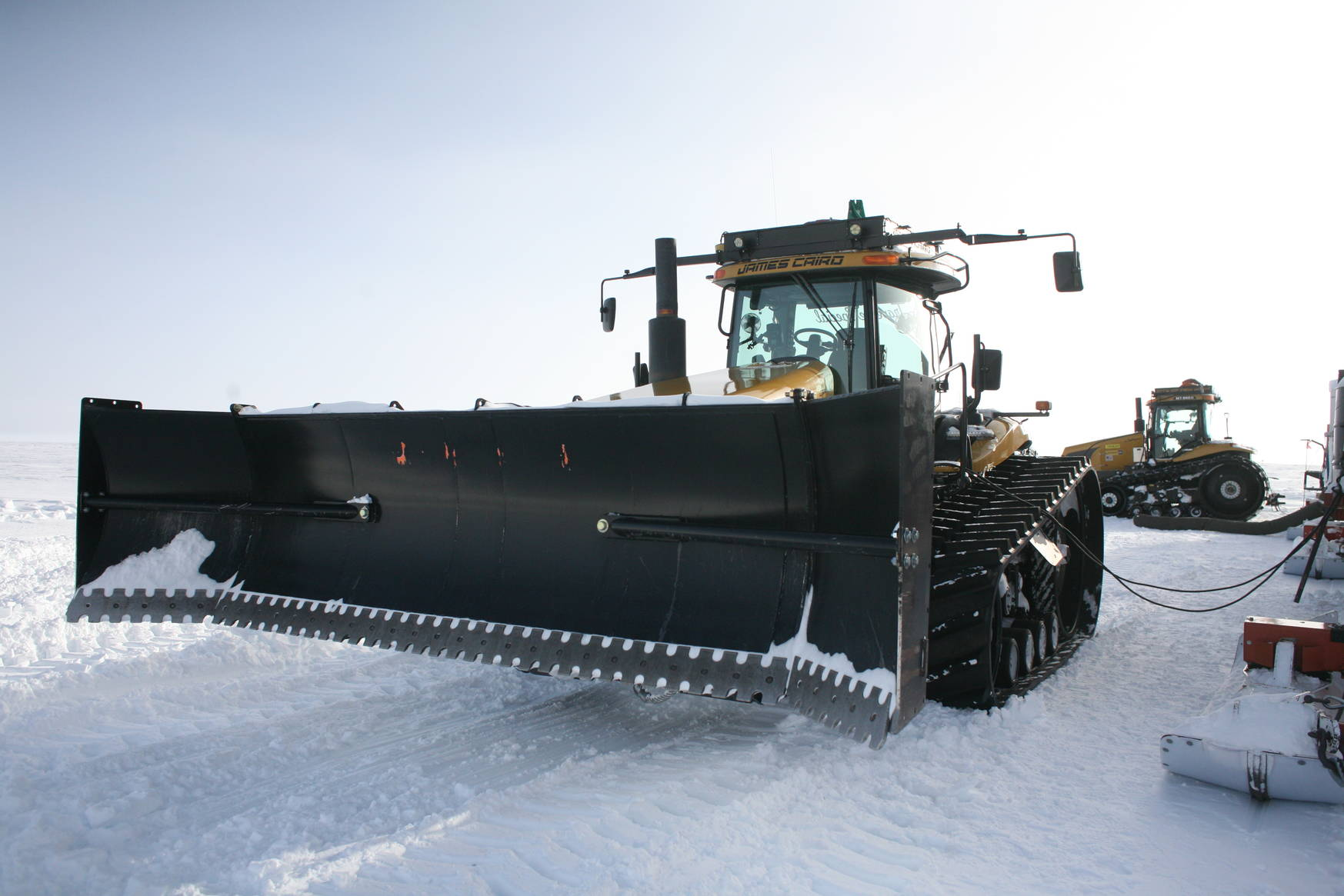 Huge tractors indeed. Here you see one that is equipped with a blade to clear the path of snow drifts.