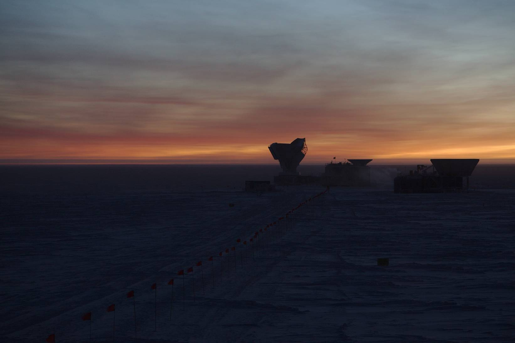 April 2017: The South Pole Telescope during EHT observations, 12 hours after the previous telescope picture. The last glimpses of the Sun behind the horizon cause the clouds in the sky to light up in hauntingly beautiful colours.