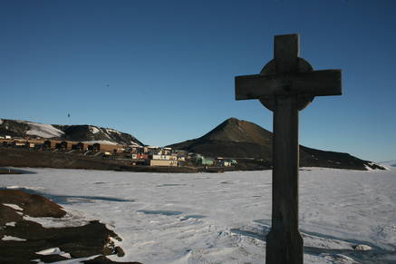 A view of the cross on top of the <em>Hut Point</em> hill. In the background the McMurdo base and the <em>Observation Hill</em>, my next hiking goal.