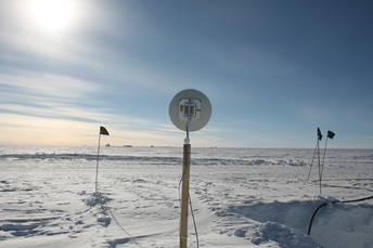 The antenna provides network connections with the station. At the horizon you can see, very small, the South Pole Telescope and the station.